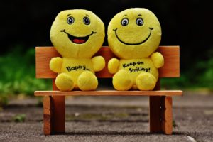 Two happy faces sitting on a bench